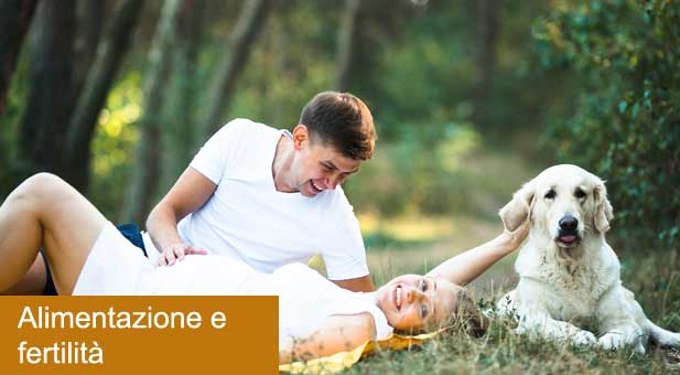 pregnant-woman-with-husband-lying-in-the-park-PUCUX3U